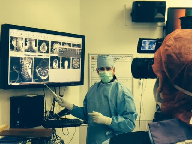 Surgeon in scrubs and mask explaining scans on screen to surgeon holding camera