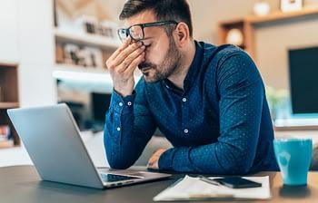 Man experiences headache while working