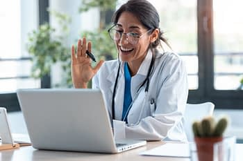Doctor smiling and waving at laptop for video call