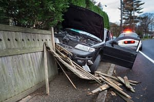 car crashed into wooden fence with police on the scene